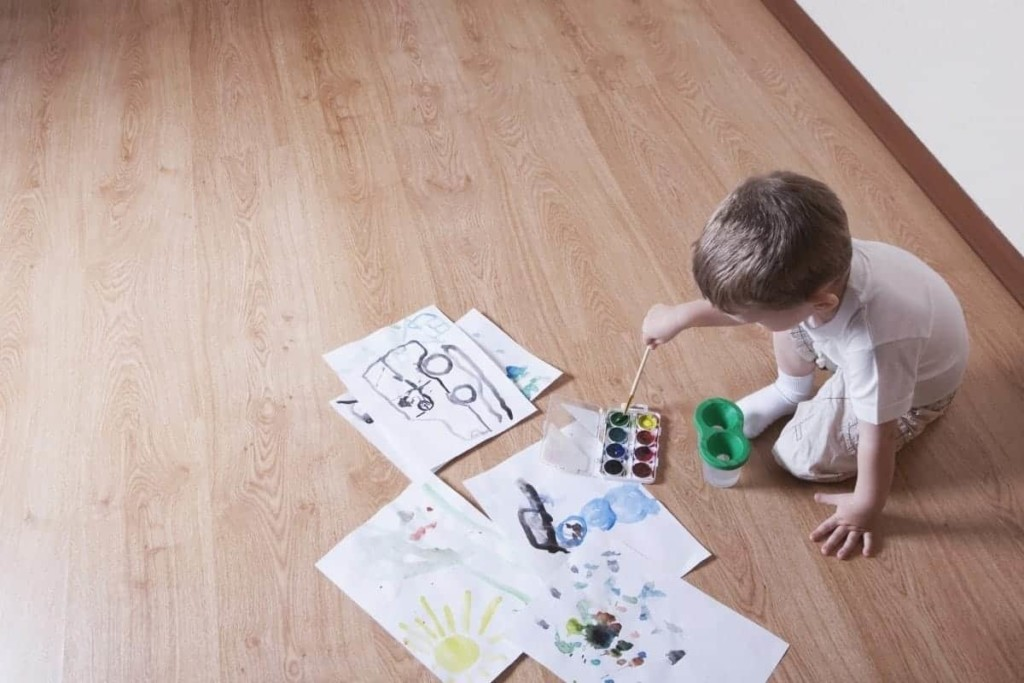 young boy painting on floor