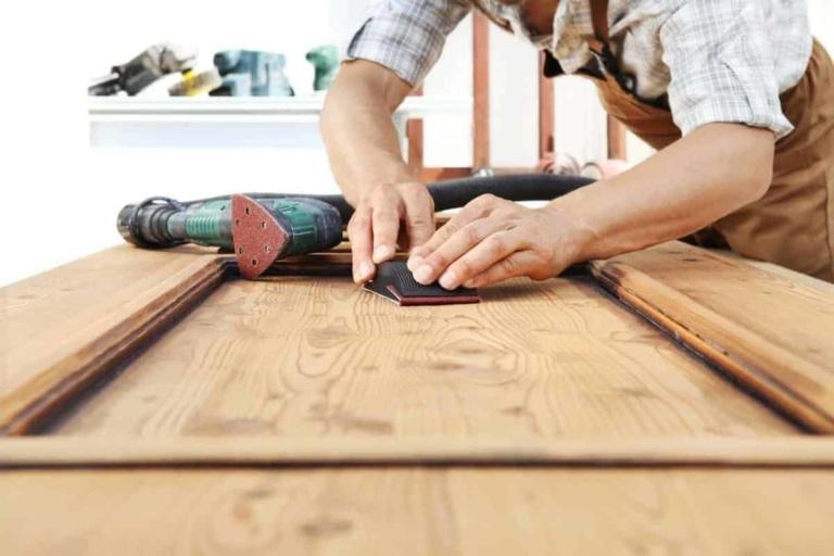 carpenter using detail sander