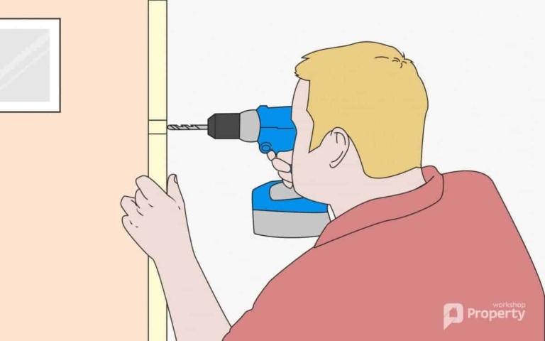 man drilling holes on a door