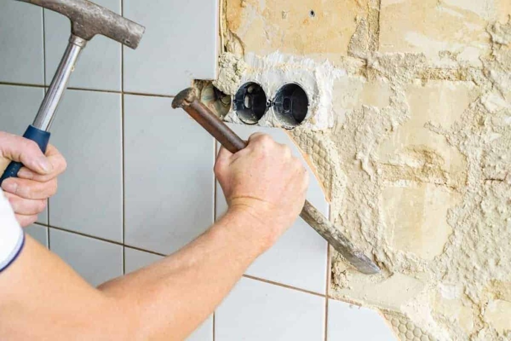 man removes wall tiles with hammer and chisel