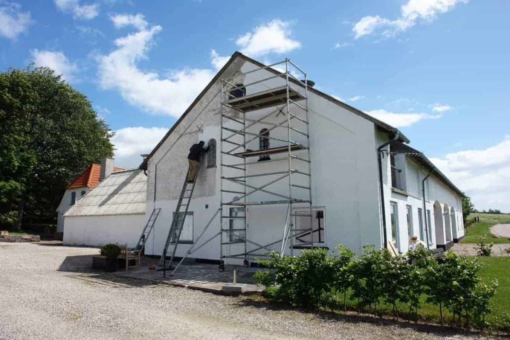 man painting house exterior with white paint