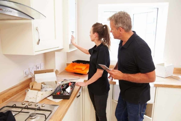 man and a woman fitting a new kitchen