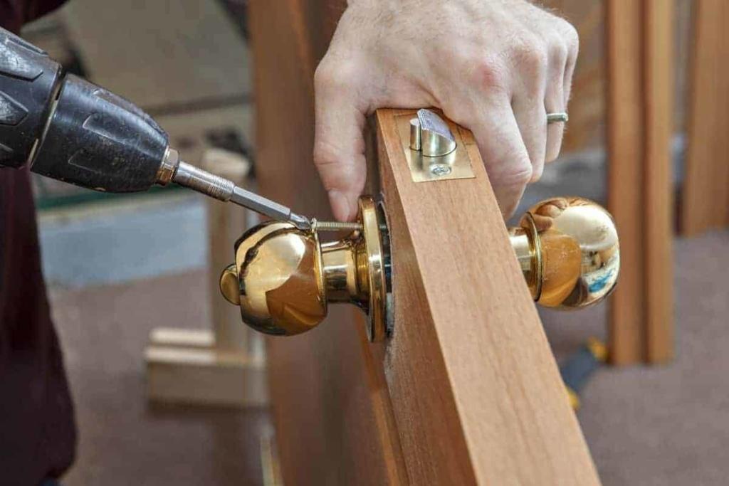 carpenter screwing door knob to door