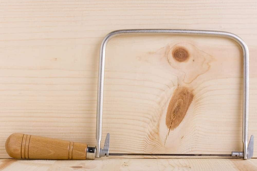 coping saw resting on wood