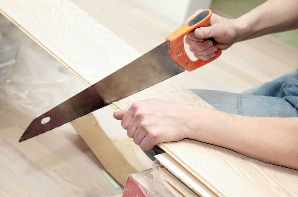 man sawing blanks of wood with handsaw
