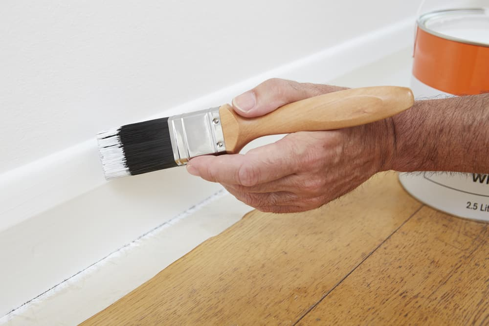 painting skirting board with white oil-based paint