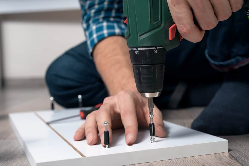 close-up of male hands assembling furniture with a screwdriver
