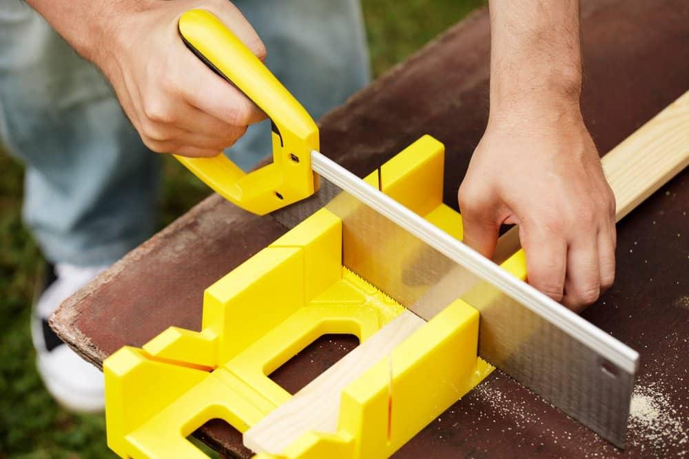 man using tenon saw to cut wood
